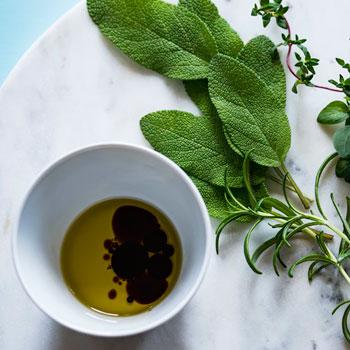 aceites naturales y hierbas orgánicas en un plato de mármol blanco