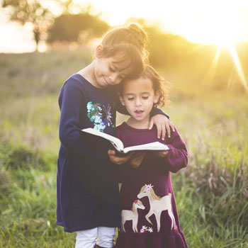 Niña mayor abrazando a una niña menos en el campo, me esta enseñando un libro