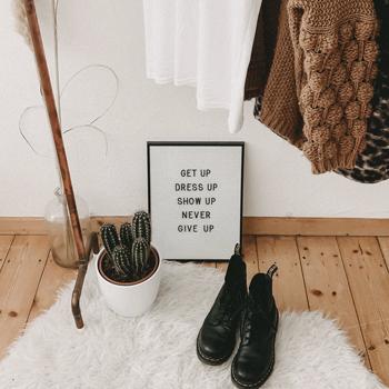 zapatos negros y ropa colgada café, banca y negra, en el suelo de madera hay una alfombra blanca peluda, en el centro se ve un letrero que indica una leyenda sostenible