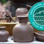 Ceramicas en greda sobre una mesa al lado de un artesano haciendo las estructuras con sello de origen de INAPI Chile