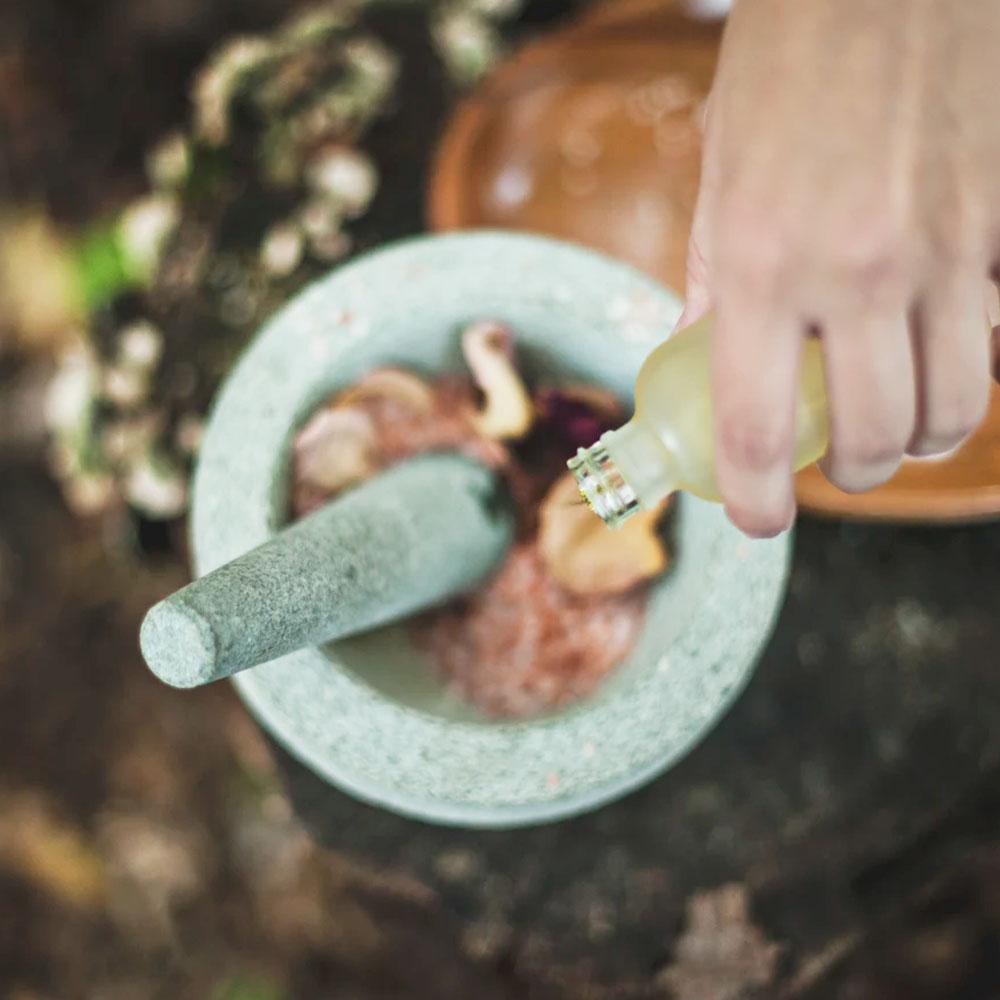 mano con una botella en la mano vertiendo aceite sobre petalos de flores en un cuenco de piedra