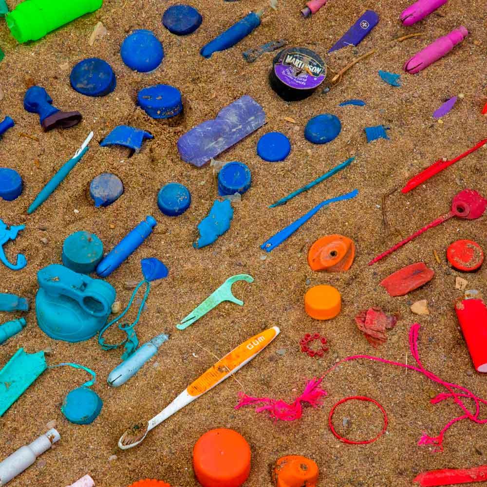 restos de productos o basura organizdos por color sobre la arena